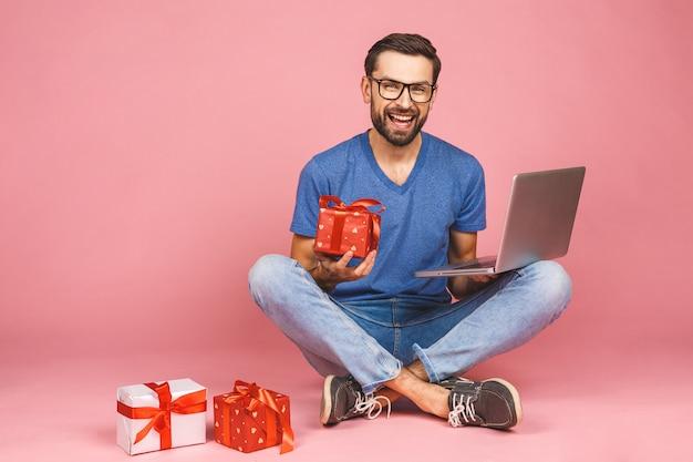 Entzückendes foto des attraktiven jungen mannes mit dem schönen lächeln, das geburtstagsgeschenkkästen lokalisiert über rosa wand hält, die auf dem boden sitzt. geschenkkonzept. laptop benutzen.
