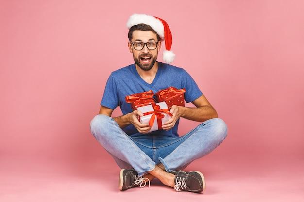 Entzückendes foto des attraktiven jungen mannes mit dem schönen lächeln, das geburtstagsgeschenkkästen lokalisiert über rosa wand hält, die auf dem boden sitzt. geschenkkonzept.