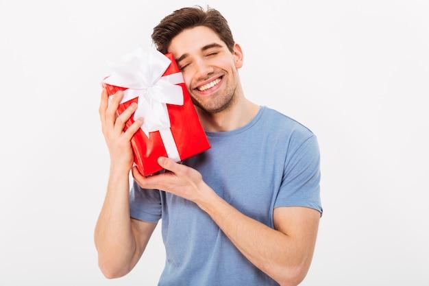 Entzückendes foto des attraktiven mannes mit dem schönen lächeln, das seinen kopf zur geburtstagsgeschenkbox lehnt, lokalisiert über weißer wand