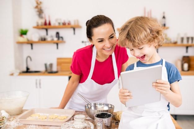 Entzückendes freudiges kind mit touchpad, das seiner mutter das videorezept von etwas wirklich leckerem zeigt, während es wählt, was gekocht werden soll