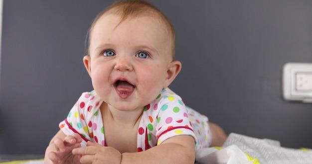 Entzückendes gesicht verziehendes lustiges baby im spielanzug, der die zunge liegt auf meinem magen auf allen vieren zeigt, die das plaid ist, das weg schaut