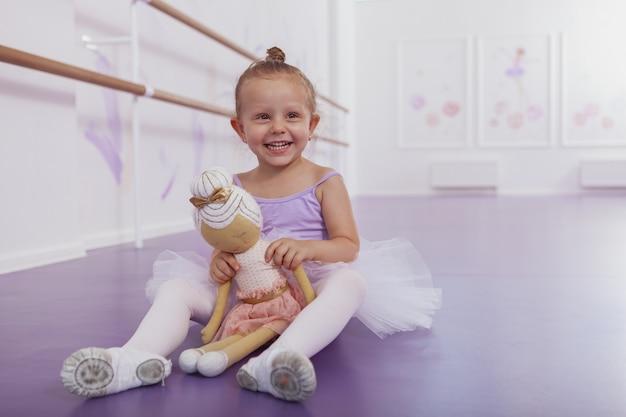 Entzückendes glückliches kleines ballerina-mädchen, das zur kamera lacht und mit ihrer ballerina-puppe im tanzstudio aufwirft