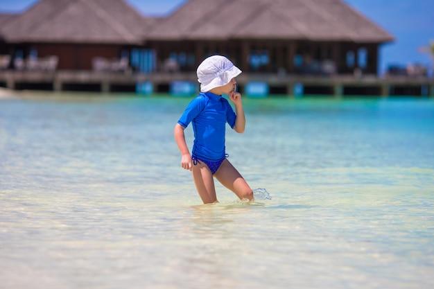 Entzückendes glückliches kleines mädchen, das am seichten wasser an den tropischen ferien spielt