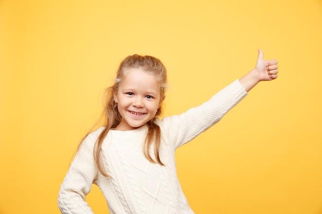 Entzückendes glückliches kleines mädchen, das lokal auf gelb steht