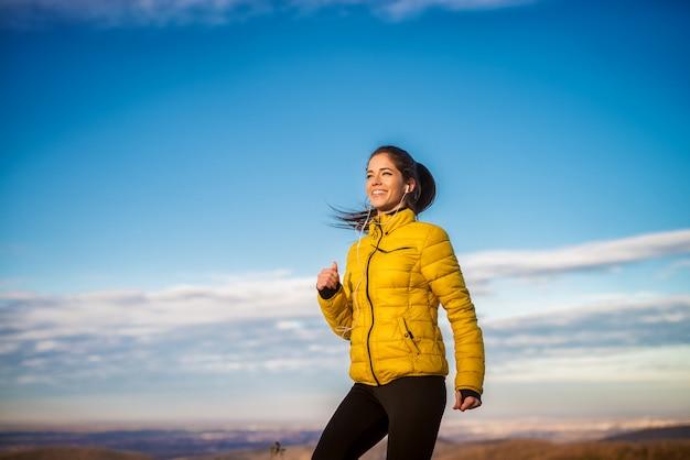 Entzückendes glückliches lächelndes sportliches mädchen, das draußen in der wintersportkleidung mit kopfhörern joggt.