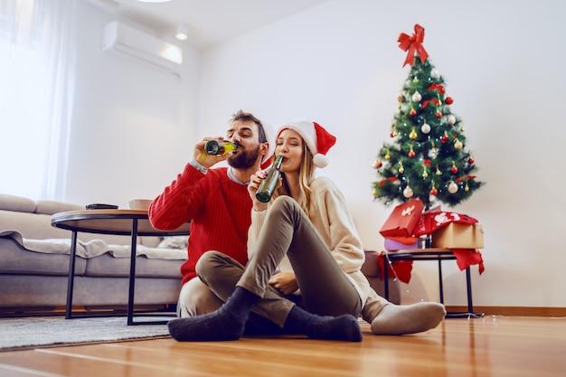 Entzückendes gut aussehendes kaukasisches paar mit weihnachtsmützen auf köpfen, die auf boden im wohnzimmer sitzen und bier trinken. im hintergrund ist weihnachtsbaum mit geschenken.