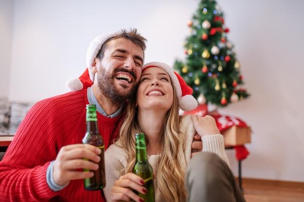 Entzückendes gutaussehendes kaukasisches paar mit weihnachtsmützen auf köpfen, die auf boden im wohnzimmer sitzen, bier umarmen und halten. im hintergrund ist weihnachtsbaum mit geschenken.