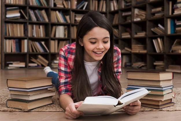 Entzückendes junges mädchen, das an der bibliothek studiert