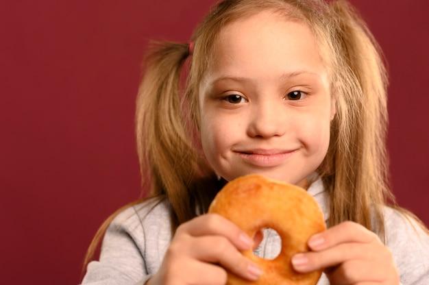 Entzückendes junges mädchen, das köstlichen donut hält