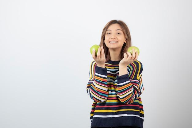 Entzückendes junges mädchen in der freizeitkleidung, die grüne äpfel auf weiß hält.