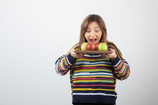 Entzückendes junges mädchen in freizeitkleidung, das haufen äpfel isst.