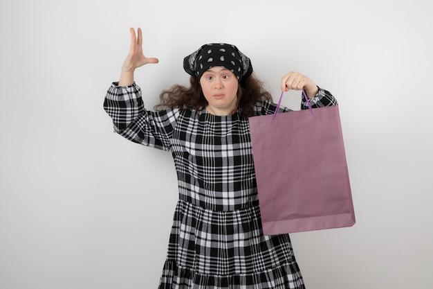 Entzückendes junges mädchen mit down-syndrom, das einkaufstasche hält.