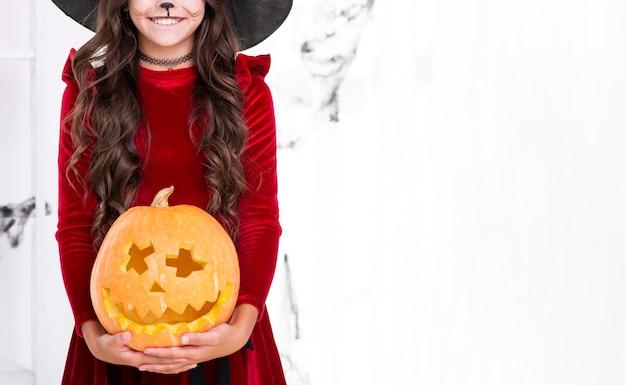 Entzückendes junges mädchen mit geschnitztem kürbis für halloween