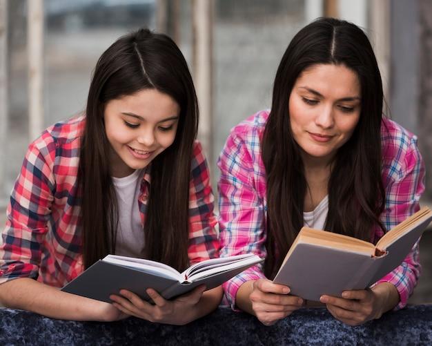 Entzückendes junges mädchen und frau, die bücher lesen