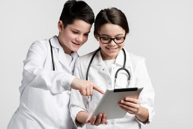 Entzückendes junges mädchen und junge verkleidet als mediziner