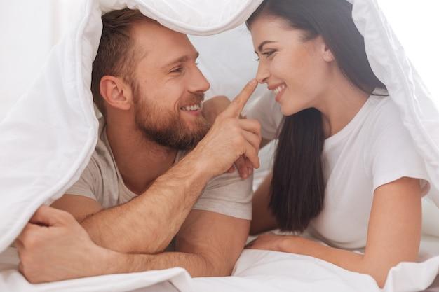 Entzückendes junges paar, das unter der decke liegt und ein kissengespräch hat, während ein mann seine frauennase berührt