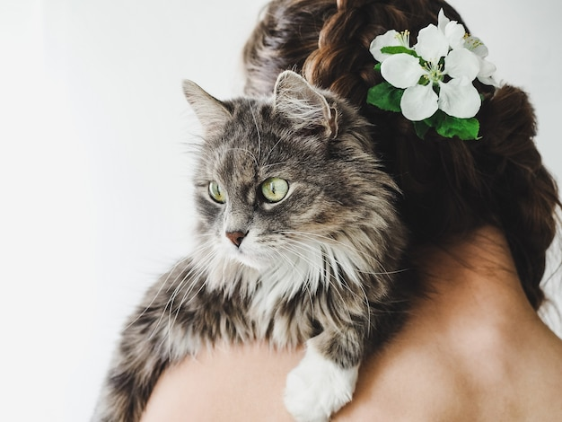 Entzückendes kätzchen, das auf der schulter einer schönen frau liegt