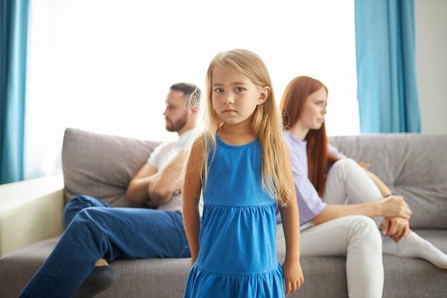 Entzückendes kaukasisches kindermädchen zwischen depressiven eltern