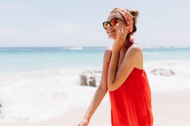 Entzückendes kaukasisches mädchen, das sommer an exotischem ort nahe meer verbringt. foto im freien der anmutigen lächelnden dame in der sonnenbrille, die im strand aufwirft