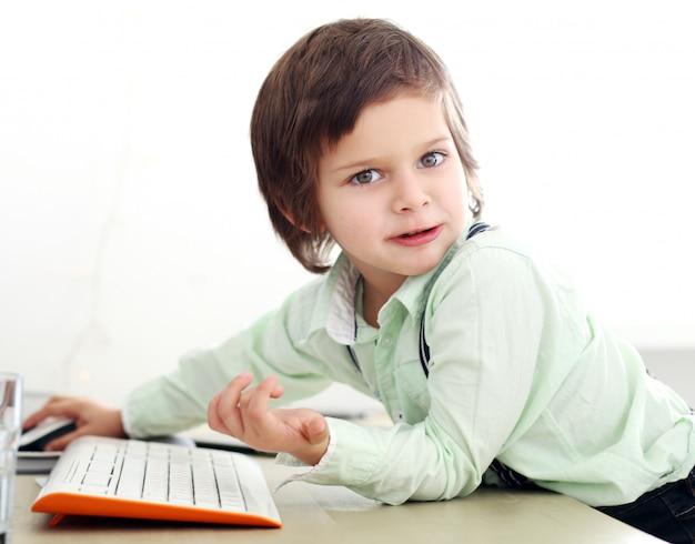 Entzückendes kind, das einen computer verwendet
