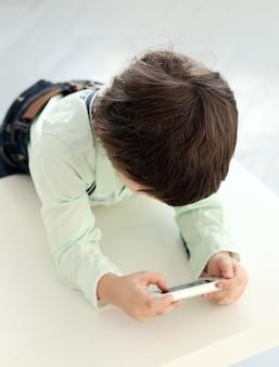 Entzückendes kind, das mit einem smartphone spielt