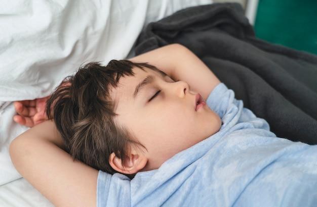 Entzückendes kind, das morgens tief im bett schläft, kind, das auf bett schläft.