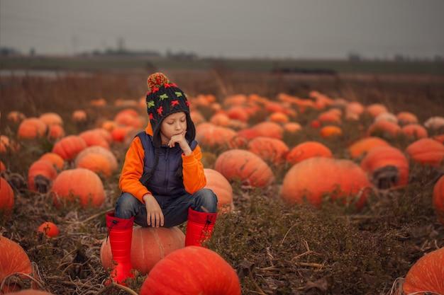 Entzückendes kind, das spaß mit kürbis auf pumpkinpatch auf bauernhof hat.