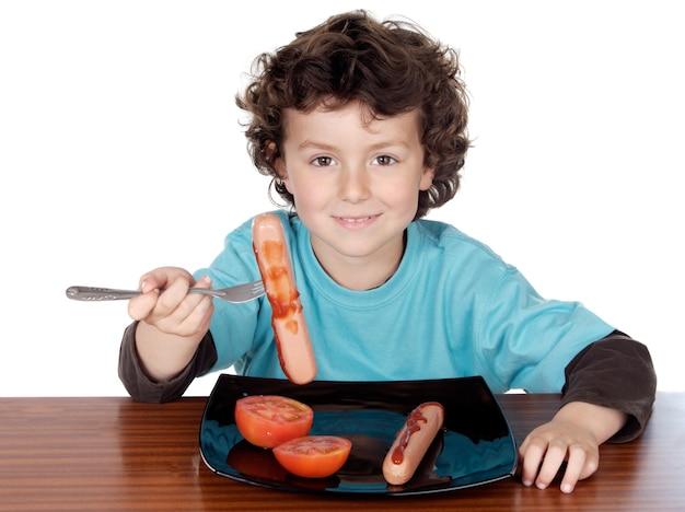 Entzückendes kind, das über weißem hintergrund isst