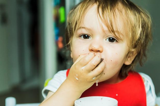 Entzückendes kind des porträts, das schokoladenschwammkuchen isst