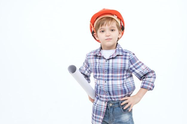 Entzückendes kind gekleidet als vorarbeiter im orange sturzhelm und in hemd, die papierentwürfe in den händen betrachten kamera halten