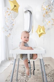 Entzückendes kind im hochstuhl geburtstag feiernd