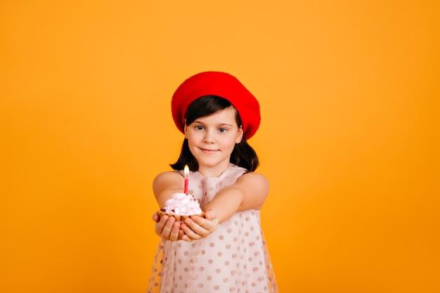 Entzückendes kind in der stilvollen baskenmütze, die geburtstag feiert. kaukasisches weibliches kind, das kuchen mit kerze lokalisiert auf gelber wand hält.