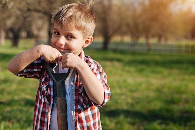 Entzückendes kind mit haselnussbraunen augen, das ein kariertes hemd trägt, sich auf eine schaufel stützt und in die front schaut