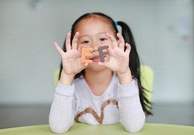 Entzückendes kleines asiatisches kindermädchen, das alphabetbuchstaben auf ihrem gesicht hält