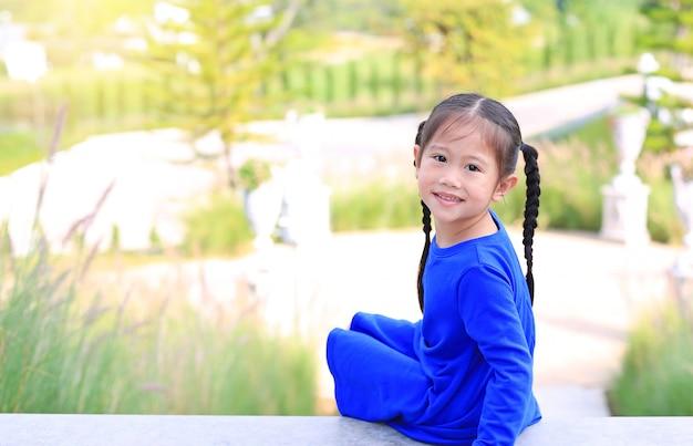 Entzückendes kleines asiatisches kindermädchen, das auf treppe im garten mit dem schauen der kamera sitzt.