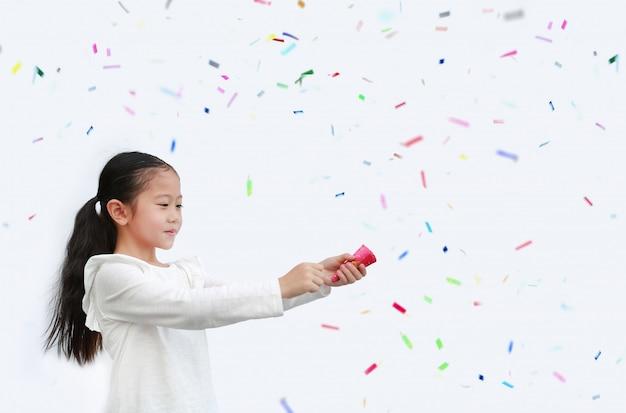 Entzückendes kleines asiatisches kindermädchen, das party-popper-konfetti mit kopierraum schießt.