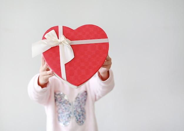 Entzückendes kleines asiatisches kindermädchen, das rote herzgeschenkbox auf weißem hintergrund zeigt. kind, das rote herzgeschenkbox für sie gibt. konzept der liebe.