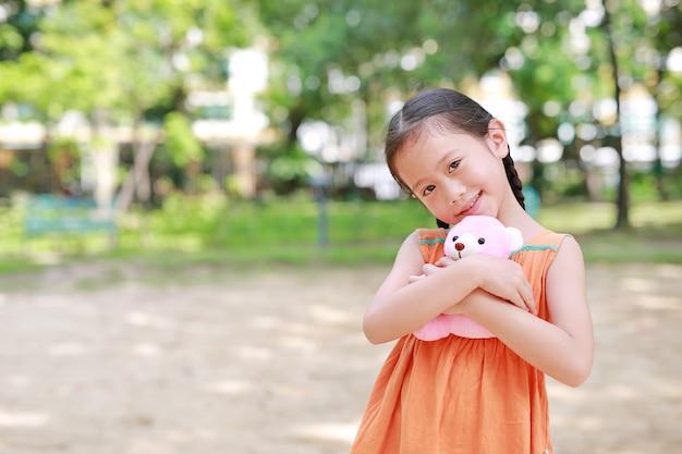 Entzückendes kleines asiatisches kindermädchen, das teddybärpuppe im garten mit dem betrachten der kamera umarmt. schließen sie herauf glückliches kind im sommerpark.