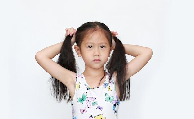 Entzückendes kleines asiatisches kindermädchen, das zopf auf weißem hintergrund hält. porträt von kindern mit zwei zöpfen.