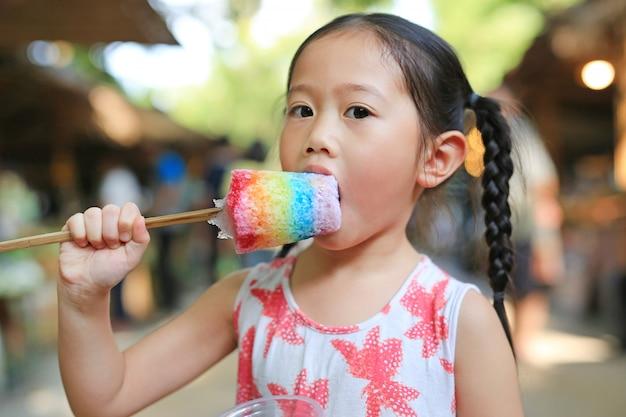 Entzückendes kleines asiatisches kindermädchen genießen, bunte thailändische arteiscreme zu essen.