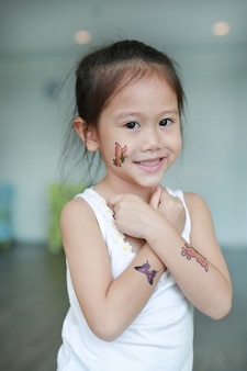 Entzückendes kleines asiatisches kindermädchen mit schmetterlingstätowierungsaufkleber auf backe und armen, kleiden oben t an