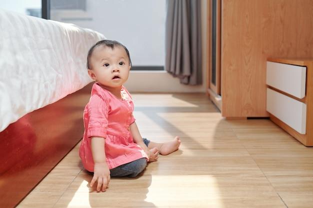 Entzückendes kleines asiatisches mädchen, das auf dem boden im schlafzimmer ihrer eltern sitzt