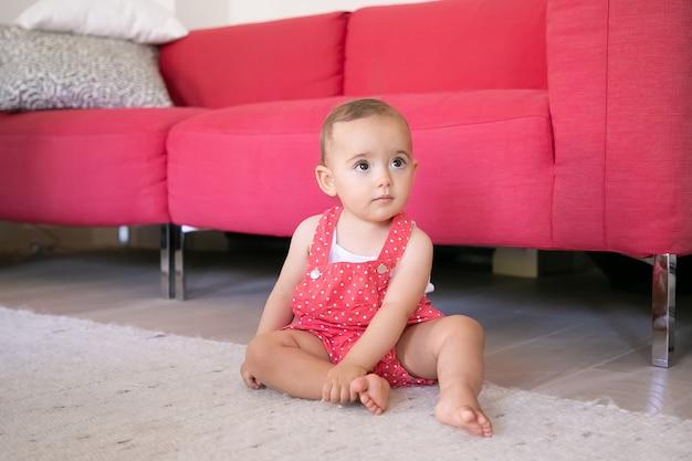Entzückendes kleines baby, das auf teppich barfuß im wohnzimmer sitzt. lustiges nachdenkliches mädchen in roten latzhose, die jemanden ansieht und ihr bein berührt. wochenende, kindheit und zuhause sein konzept