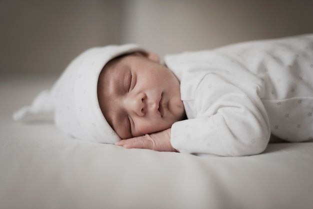 Entzückendes kleines baby, das auf weißen blättern schläft