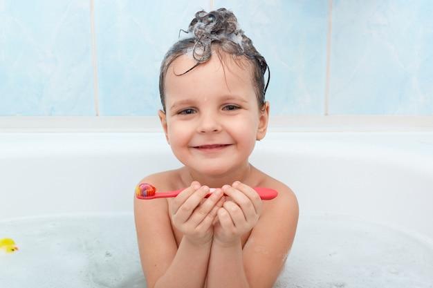 Entzückendes kleines baby, das ihre zähne putzt, bad allein nimmt, süßes kleines kind, das froh ist, sich zu waschen