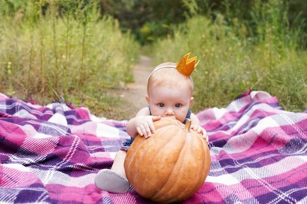 Entzückendes kleines baby, das spaß mit kürbis an einem schönen herbsttag im freien hat. glückliches kind, das im herbstpark spielt