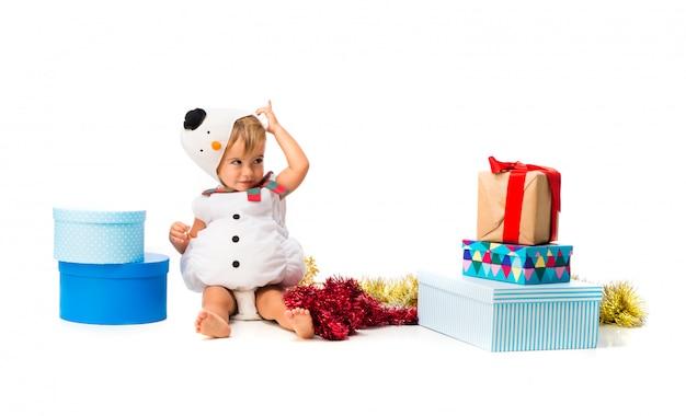 Entzückendes kleines baby kleidete wie ein schneemann an den weihnachtsfeiern auf lokalisiertem weißem hintergrund an