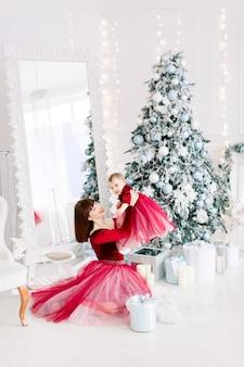 Entzückendes kleines baby lachend, während ihre charmante junge mutter sie über kopf hält
