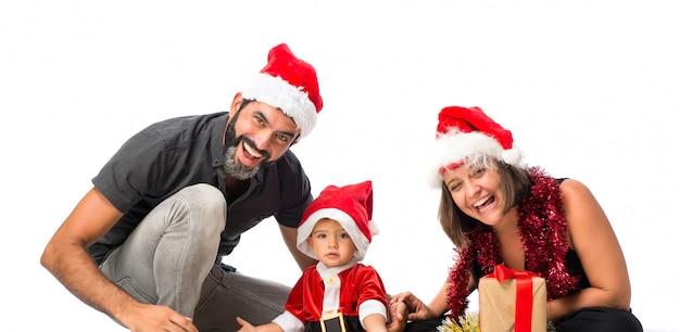 Entzückendes kleines baby mit seinen eltern an den weihnachtsfeiern auf lokalisiertem weißem hintergrund