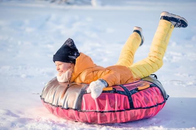 Entzückendes kleines glückliches mädchen, das am schneebedeckten tag des winters rodelt.